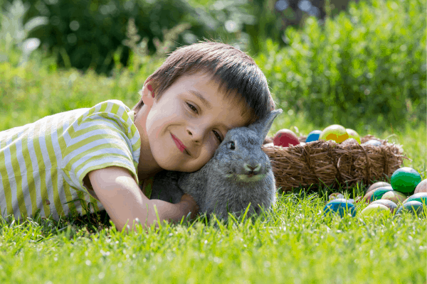 boy with basket of eggs and bunny for easter basket ideas for boys