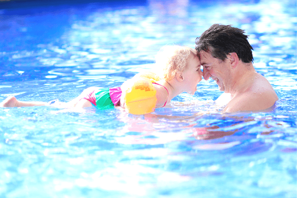 father holding his young daughter face to face in swimming pool