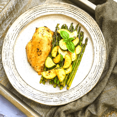 sheet pan roasted chicken and summer veggies on a plate