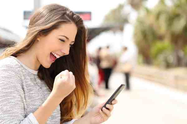 Woman using her smart phone to earn money by referring friends to her favorite programs.