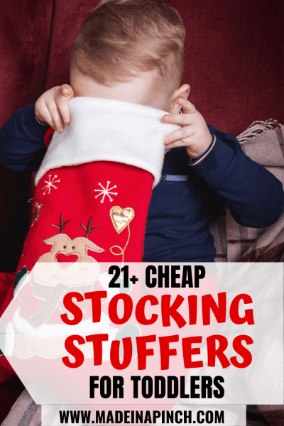 Toddler boy looking into his Christmas stocking for one of the top toddler stocking fillers ideas on this list Pinterest pin