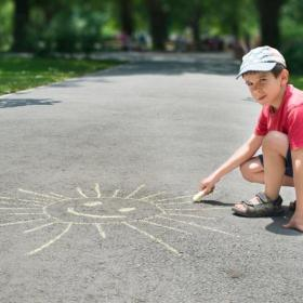 Little boy drawing a sun with chalk on the sidewalk