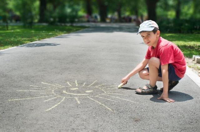 Little boy drawing a sun with chalk on the sidewalk, just one of 14 ideas of fun games to play when bored at home
