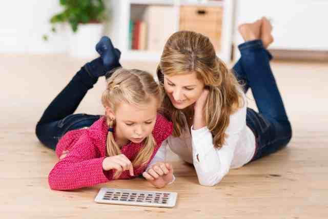 mom and daughter on the floor with a tablet exploring fun activities to do at home with kids