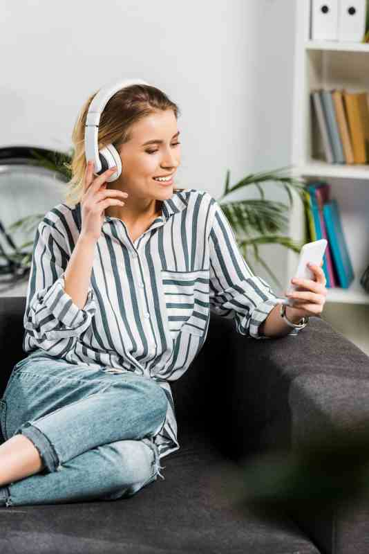 woman sitting on couch with headphones listening to podcast
