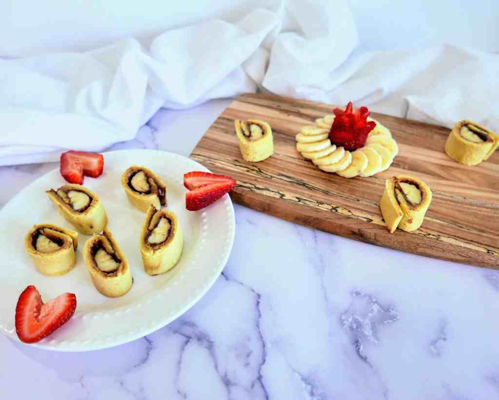 a plate and board with cut up banana sushi rolls on them.