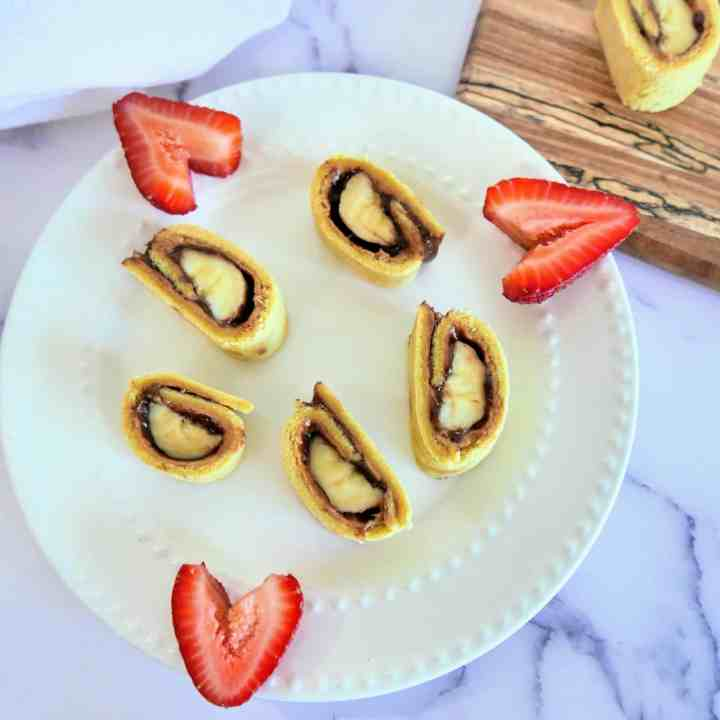 sliced banana sushi rolls on a plate with cut up strawberries