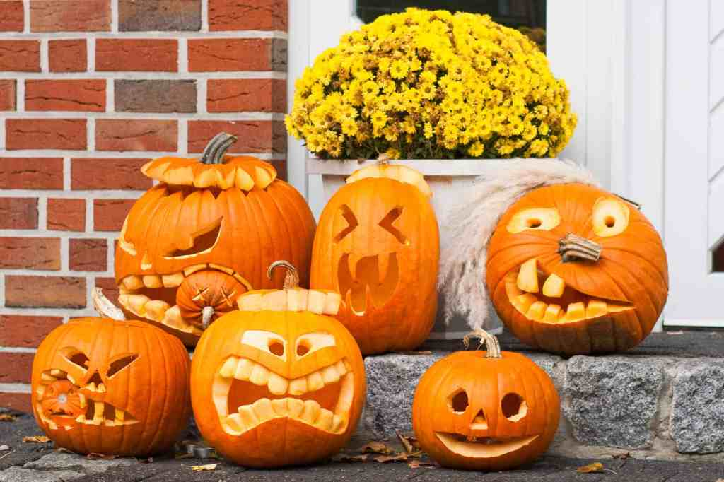collection of six different jack-o-lanterns on front porch steps