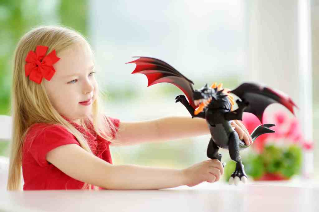 girl playing with dragon toys