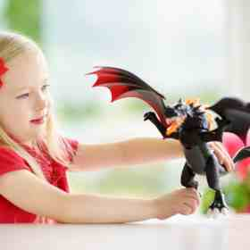girl playing with a toy dragon
