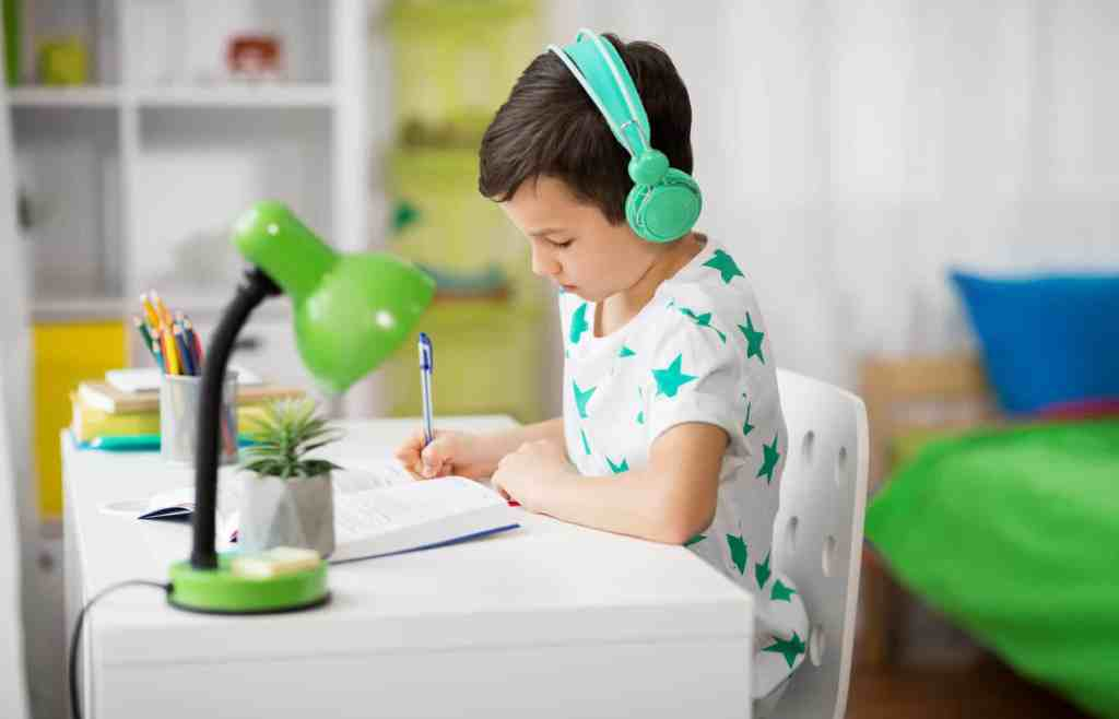 boy sitting at a desk doing schoolwork with headphones on