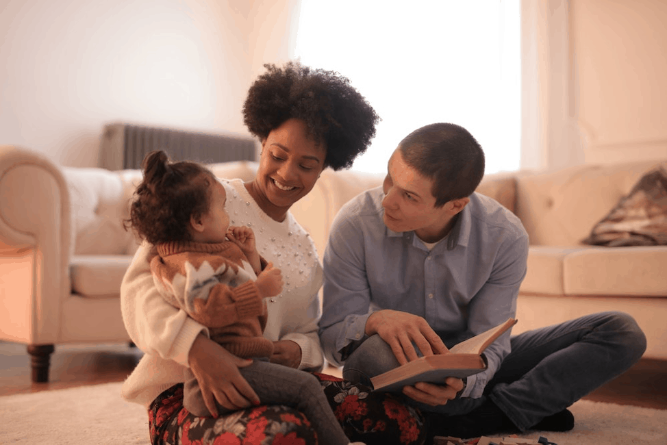 parents reading to a young girl