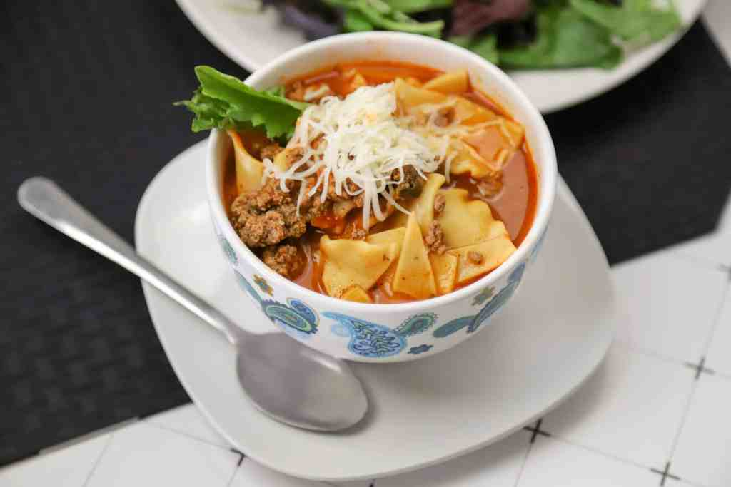 Instant pot lasagna soup in a bowl with a spoon and a side salad