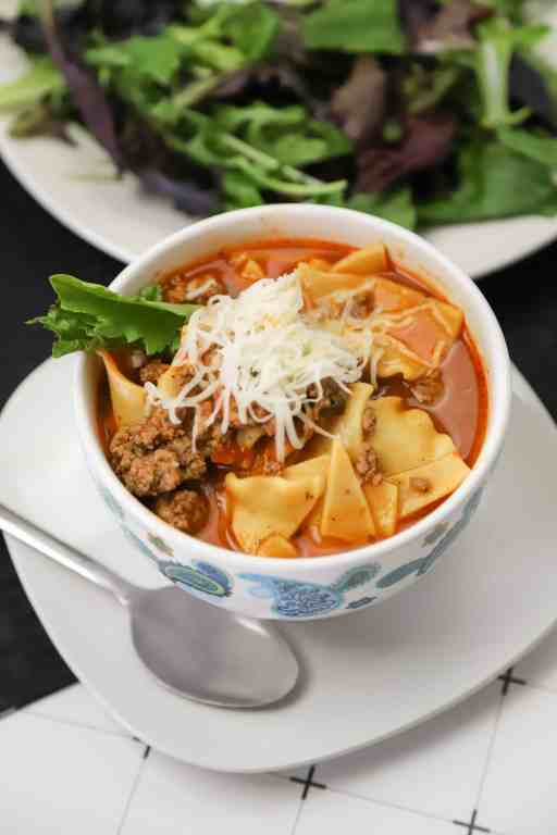 closeup of Instant pot lasagna soup in a bowl with a spoon and a side salad
