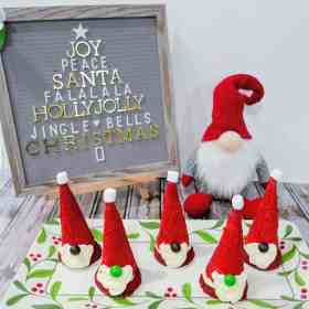 Santa gnome cookies on a tray in front of a Santa gnome and letter board