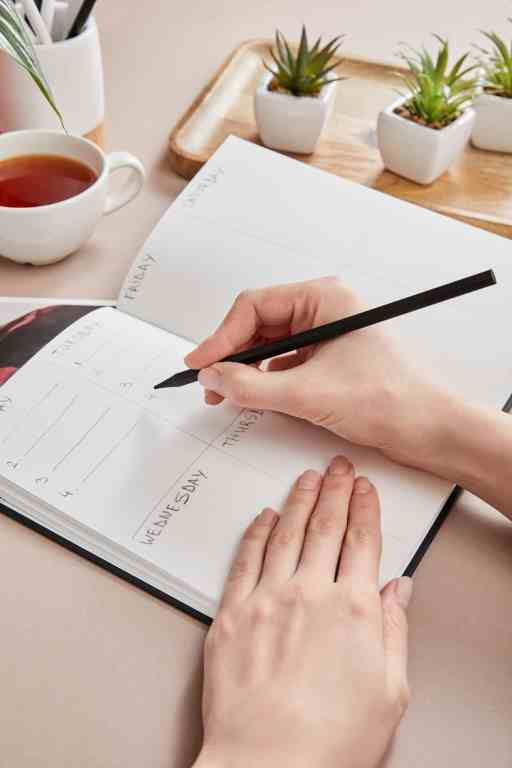 woman writing in a bullet journal which make the best planners for moms