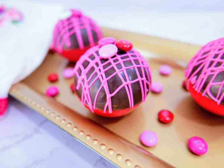 Valentine's M&M hot cocoa bombs on a gold tray closeup