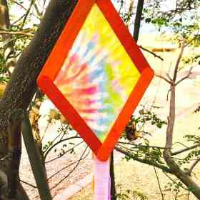 tie dye kite popsicle craft for kids hanging in a tree