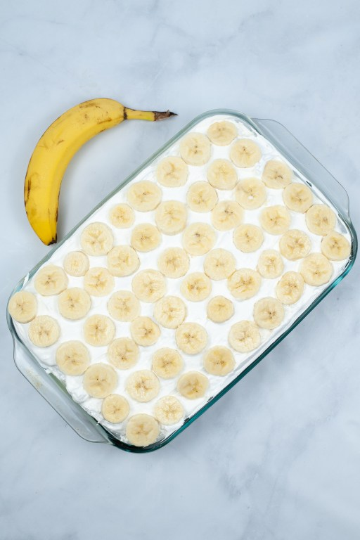 poke cake with whipped topping and sliced bananas on top