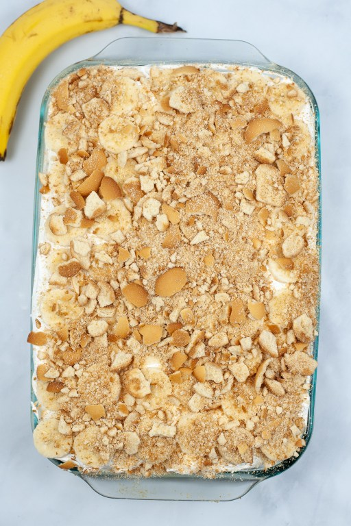 crumbled vanilla wafers on top of the banana pudding poke cake