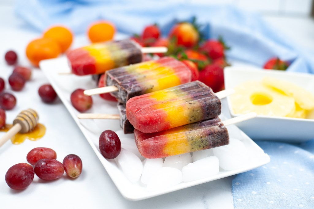 Cocomelon rainbow popsicles stacked on a plate of ice