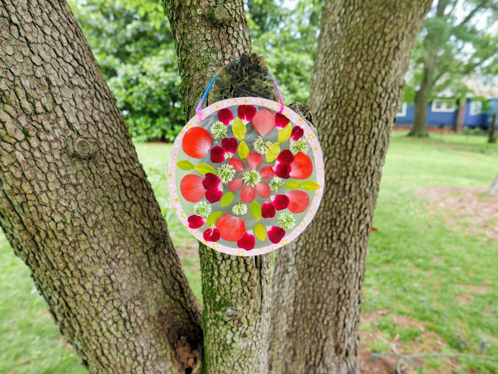 completed DIY nature mandala hanging in a tree outside
