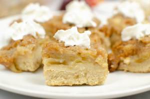 close up of apple crisp bars with whipped cream
