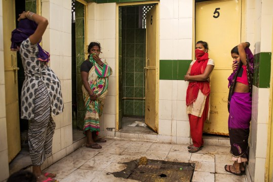 "New Delhi, Inde. Des installations collectives sont une réponse à la pénurie de toilettes en Inde, mais sans système organisé pour le nettoyage et l'entretien, la défécation reste un problème de santé publique. Ces femmes attendent l'ouverture de la seule cabine en état de marche. New Delhi, India. Community facilities are one answer to the shortage of toilets in India, but with no system for maintenance and cleaning, defecation remains a health problem. These women are waiting for the one working stall to open for use. © Andrea Bruce / NOOR Images for National Geographic Magazine Photo libre de droit uniquement dans le cadre de la promotion de la 30e édition du Festival International du Photojournalisme ""Visa pour l'Image - Perpignan"" 2018 au format 1/4 de page maximum. 