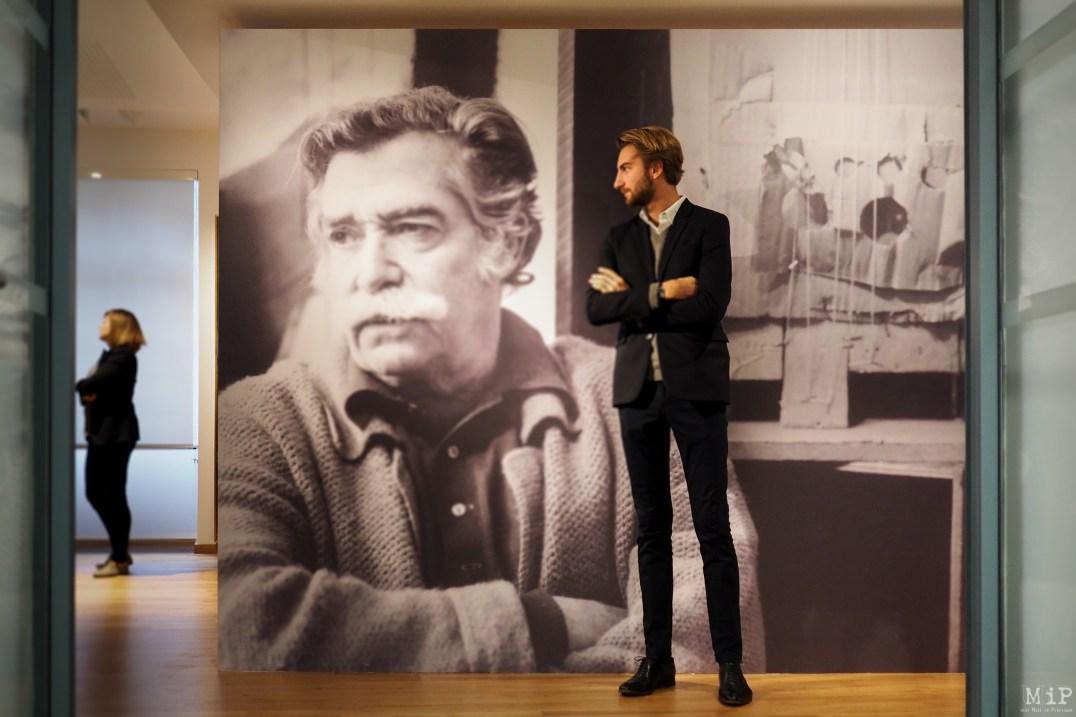 Antoine Clavé prend la pose devant la photo en noir et blanc de son illustre grand-père