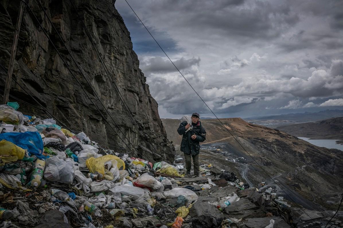 Un mineur rentre chez lui le long d'un col jonché de déchets plastique à usage unique. La Rinconada, Pérou. A miner returning home along a precipice littered with single-use plastic trash. La Rinconada, Peru. © James Whitlow Delano