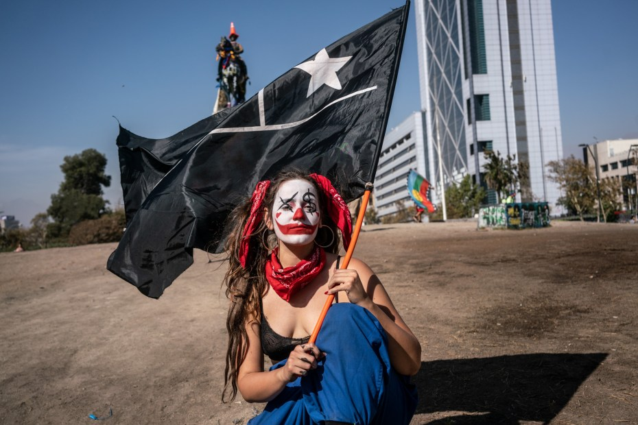 CHILI - VIVIR PARA CONTARLO Santiago de Chile. A clown-clad protester holds a totally black flag of Chile in Plaza de la Dignidad (former Plaza Italia) in memory of the street artist girl arrested by the Chilean police and found a few days later hanged in a park in the capital after being repeatedly raped. The black flag is a sign of mourning for the violence perpetrated by law enforcement and the state during the days of repression. © Karl Mancini