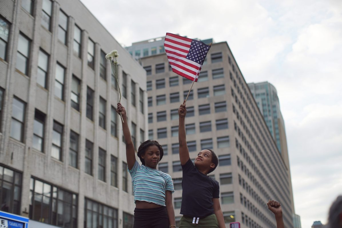 Little boy and girl holding the american flag and flowers