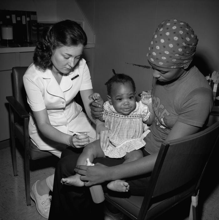 Cette image historique de 1977 montre une jeune fille afro-américaine assise sur les genoux de sa mère, sur le point de recevoir un vaccin dans la cuisse droite, administré par une infirmière de santé publique, dans un centre de soins pour bébés du comté de Dekalb, en Géorgie. © CDC PHIL Meredith Hickson