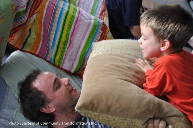 Father and Son playing together with big pillow.