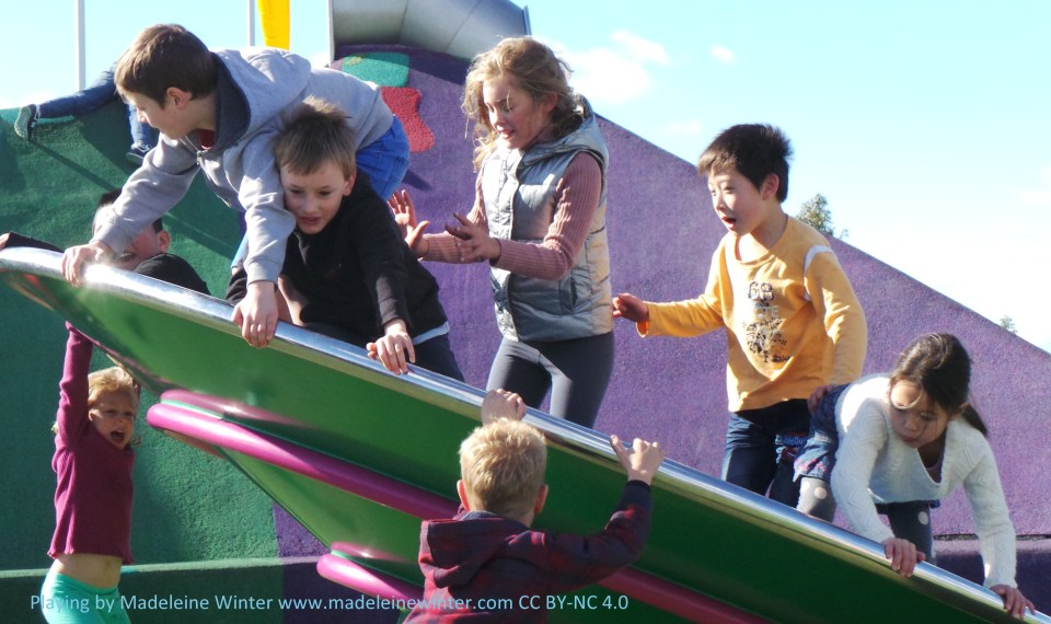 Children playing on roundabout wheel.