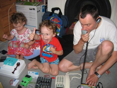 Man plays with 4 and 3 year old children - a game invoving lots of equipment - a phone, things with knobs, walkie talkies calculators etc