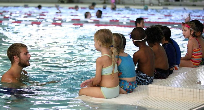 Young man swimming teacher in pool instructs children sitting in a line on edge of pool