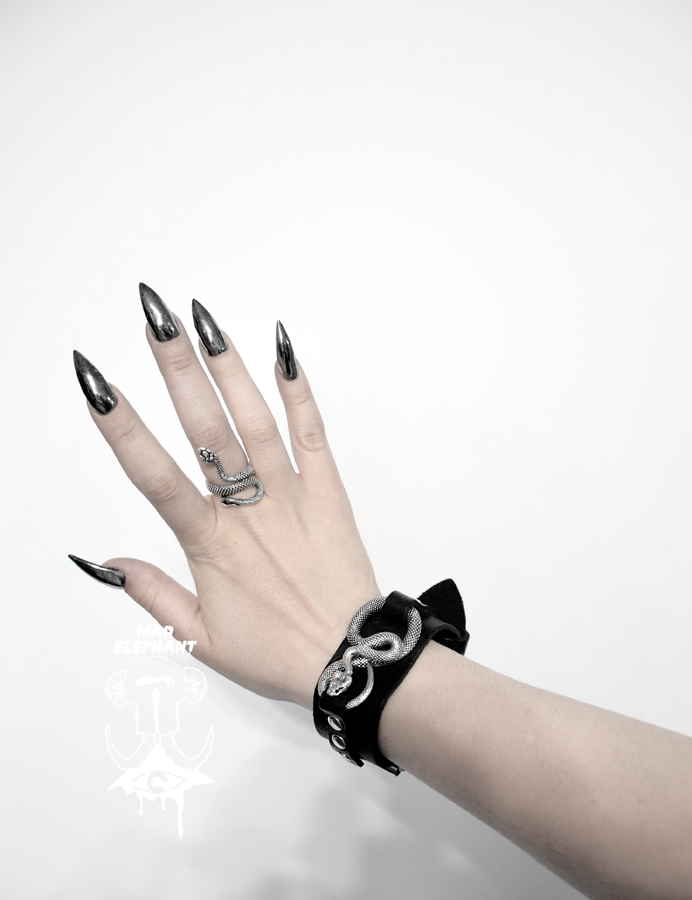 woman hand with serpent ring and leather serpent cuff