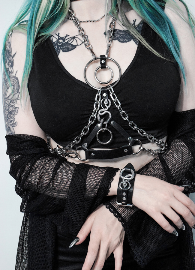 Tattooed girl in chain harness with serpent signs