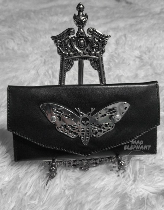 leather wallet with moth symbol on the stand