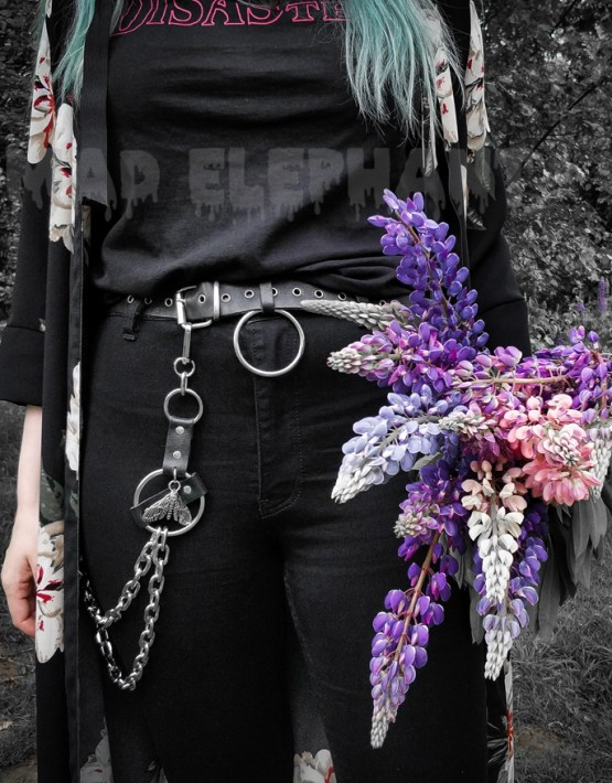 gothic girl with carabiner belt holding purple flowers