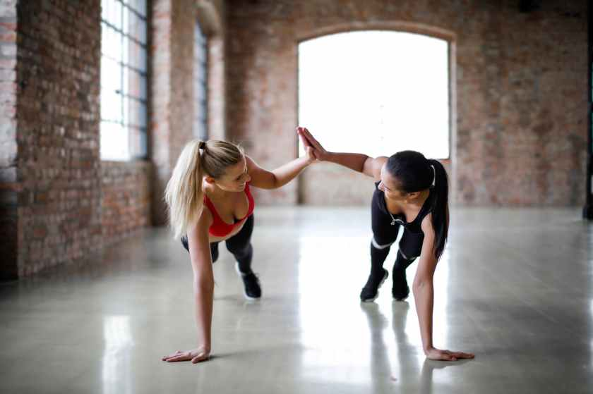 young slender female athletes giving high five to each other while training together in sports club