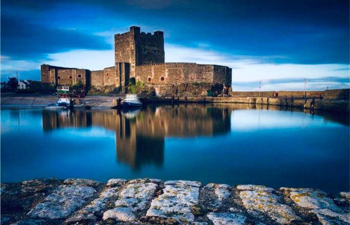 Castelli d'Irlanda: Carrickfergus Castle l'immagine raffigura la fortezza e la riva del fiume Belfast Lough che scorre davanti
