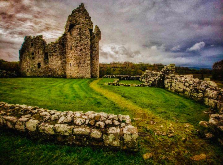 Castelli d'Irlanda: Monea Castle l'immagine raffigura i resti del castello sotto un cielo carico di nuvoloni