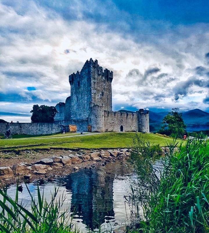 Castelli d'Irlanda: Ross Castle. L'immagine raffigura i resti della fortezza con il Kilkenny National Park sullo sfondo e il corso del lago che gli scorre davanti
