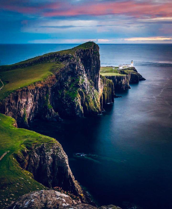 Isola di Skye: Niest Point. L'immagine delle falesie sul mare blu con il faro sullo sfondo. Il cielo che si prepara al tramonto con sfumature di azzurro e rosa che si fondono