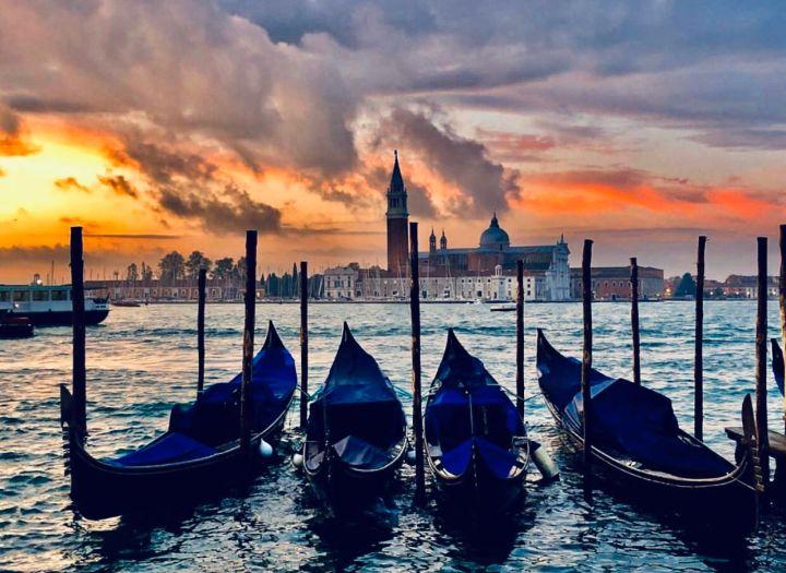 In primo piano le 4 tipiche gondole ormeggiate in piazza San Marco e sullo sfondo l'isola della Giudecca vista da Piazza San Marco, al tramonto