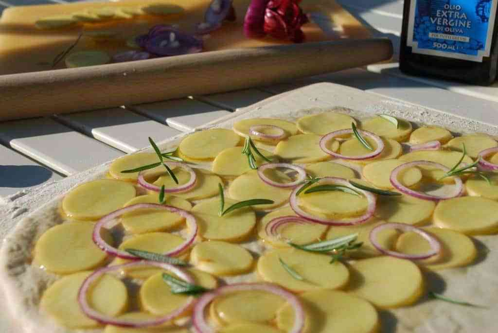 Kartoffelskiver lægges tæt og drysses med friske rosmarinkviste og rødløg. Foto: Guffeliguf.dk