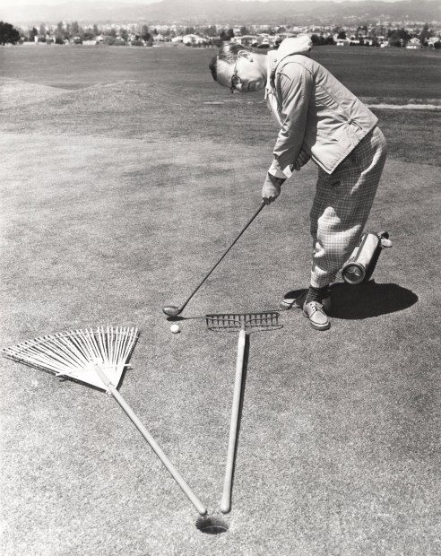 man using tools laid on ground to increase his putting ability in golf