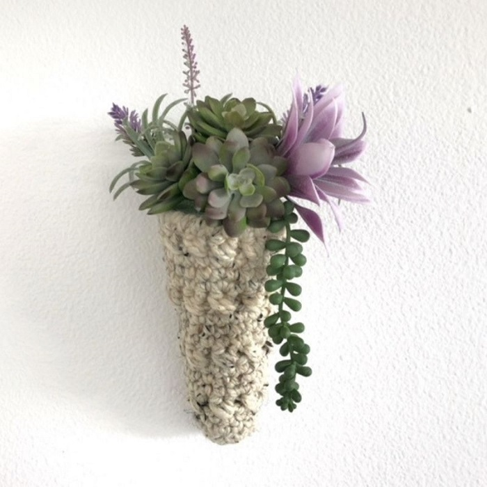a photo of a cone shaped plant hanger hanging on the wall. it hold succulents with bright green and lavender tones.